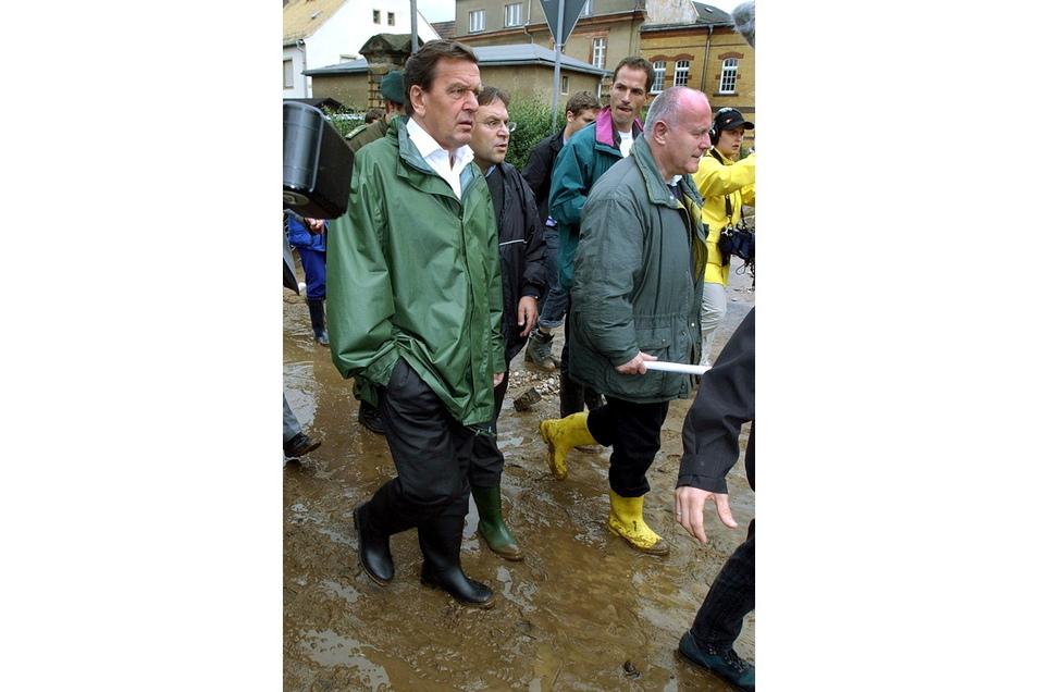 2002, Sachsen, Grimma: Der damalige Bundeskanzler Gerhard Schröder (SPD, l) und der ehemalige sächsische Ministerpräsident Georg Milbradt (CDU) gehen durch die nach einem Hochwasser verwüstete sächsische Kreisstadt Grimma.