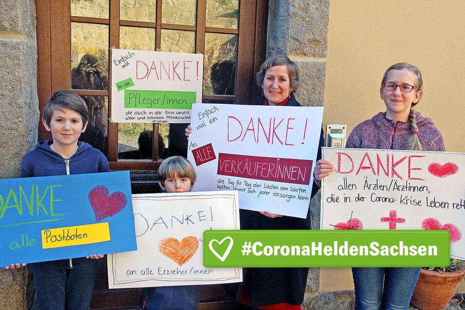 Monika Vetter und ihre Kinder Jakob, Simeon und Magdalena (v.l.) haben Plakate gebastelt, mit denen sie sich bei den Helfern in der Krise bedanken.
