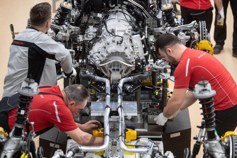 Mitarbeiter der Porsche AG montieren im Hauptwerk den Motor eines Porsche 911.