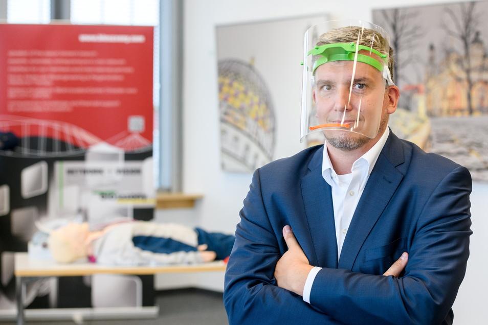 Schutzvisier aus eigener Produktion: Biosaxony-Geschäftsführer André Hofmann ließ 8.000 Halterungen herstellen – erst im 3D-Druck, dann per Spritzguss. Im Hintergrund eine Beatmungspuppe mit Technik aus dem 3D-Drucker.