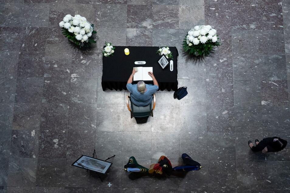 Eine Frau trägt sich im Foyer der Sächsischen Staatskanzlei in Dresden in das Kondolenzbuch ein.