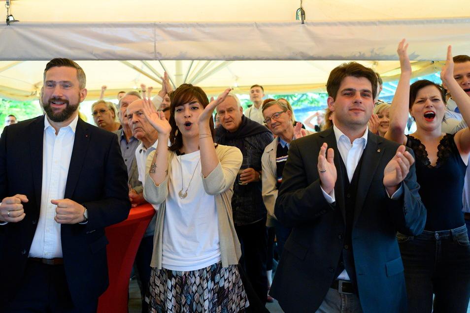 Sachsens SPD-Chef Martin Dulig jubelt mit den Dresdner Bundestagskandidaten Rasha Nasr und Stephan Schumann.