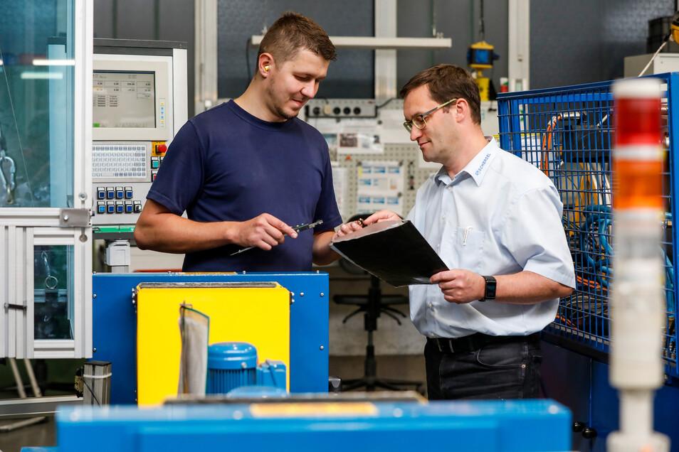 SFS-Geschäftsführer Michael Stolle (rechts) bespricht mit Mitarbeiter Stefan Weitzmann das Einrichten eines neuen Automaten, mit dem Federn für Gurtversteller hergestellt werden sollen.