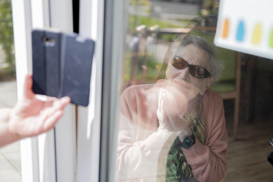 Einer Seniorenheimbewohnerin wird durch ein Fenster ein Foto aufm dem Handy gezeigt.