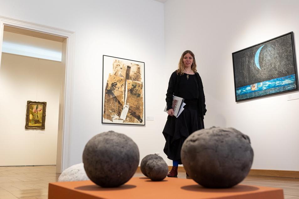 """Kristin Gäbler in der von ihr kuratierten Ausstellung """"Große Kunstschau Freital"""" mit Arbeiten von Barbara Hornich (vorn), Wolfgang Petrovsky (links) und Andreas Küchler."""