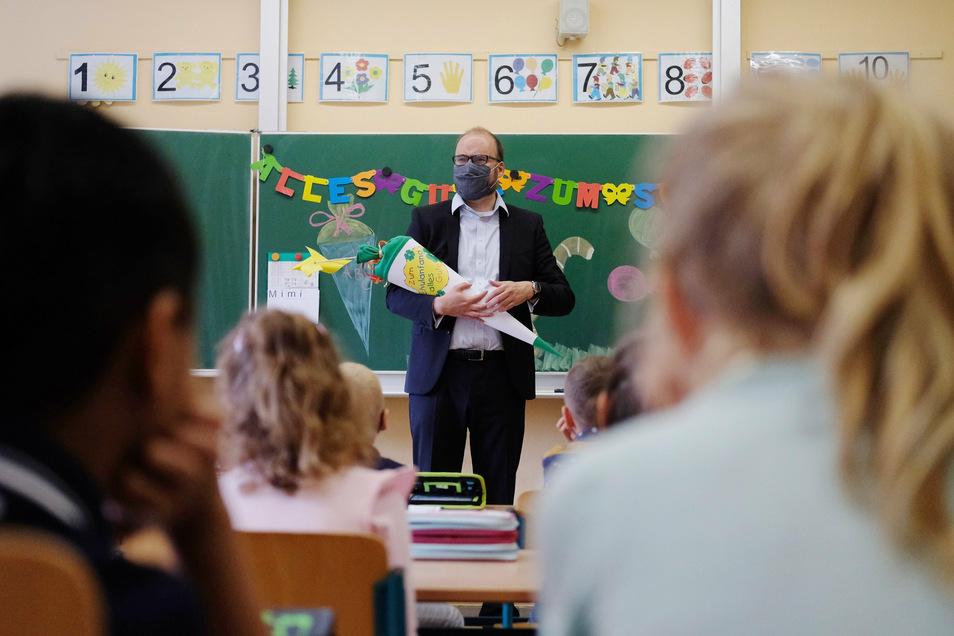 Der Mann mit der Maske, der hier die Erstklässler in Beilrode begrüßt, ist Sachsens Bildungsminister Christian Piwarz.