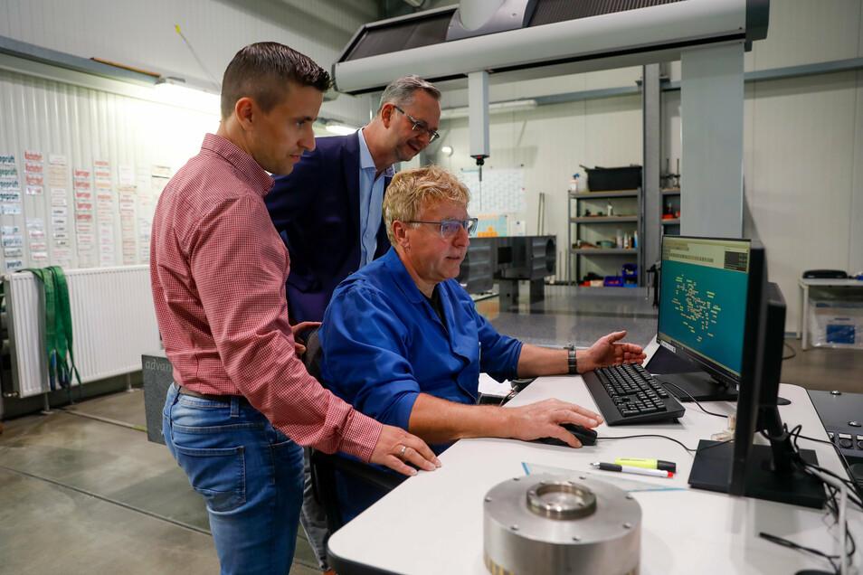 Steffen Wolf, Mitarbeiter der Qualitätssicherung bei Phänomen in Zittau (sitzend) zeigt FMA-Geschäftsführer Ralf Stirl und dem kaufmännischen Leiter Thomas Thiem (stehend von rechts), wie die Produktqualität geprüft wird.