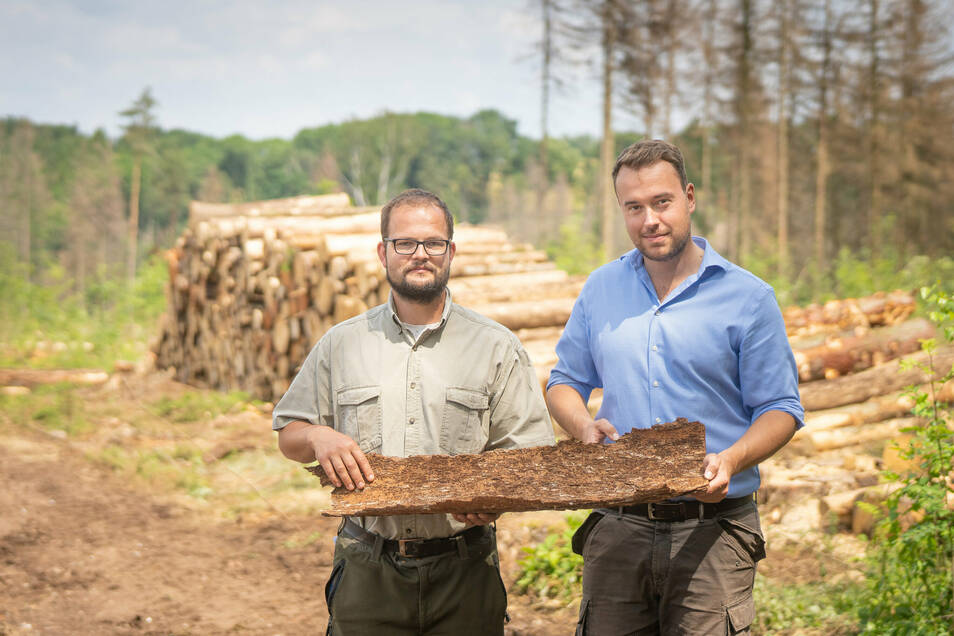 Forstsachverständiger Robin Späth und Waldbesitzer Maximilian von Schönberg mit einem Stück Rinde einer toten Fichte.