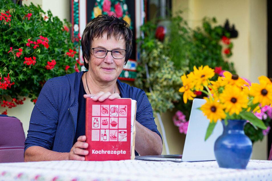 """Heide Dix vor ihrem Haus in Rehefeld mit ihrer ursprünglichen Rezeptesammlung, die die Grundlage ihres Buches """"Meine gute Küche"""" bildet."""