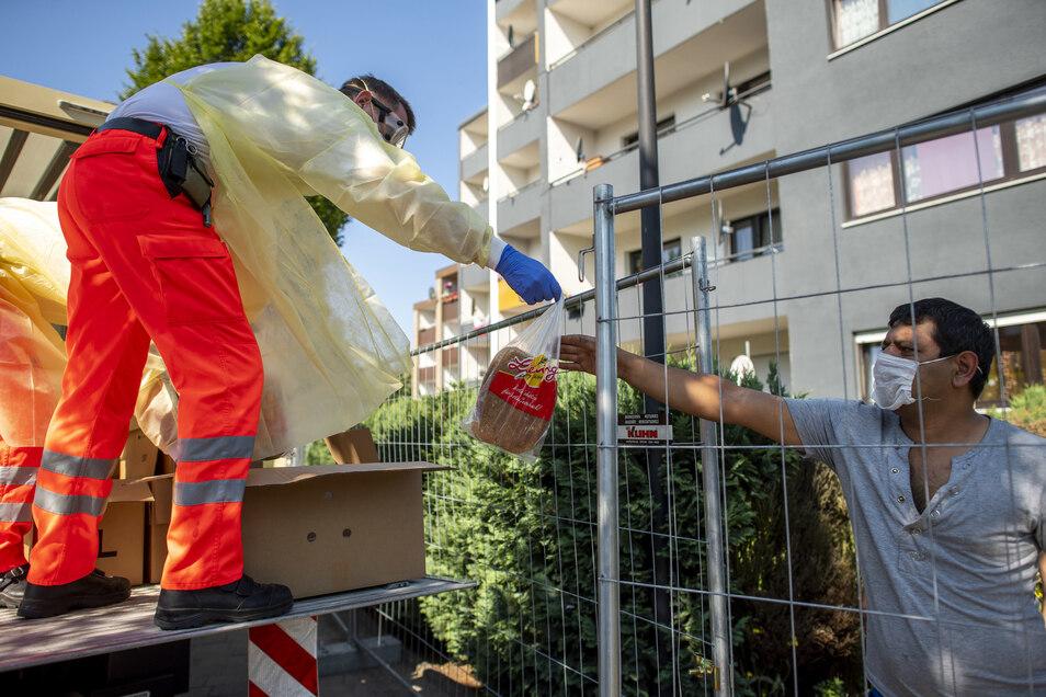 Ein Rotkreuz-Helfer überreicht in Verl einen Beutel mit Brot an einen Bewohner eines Wohnhauses, das unter Quarantäne gestellt worden ist.