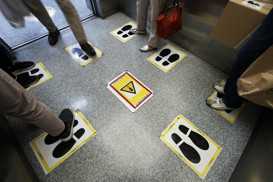 Aufkleber markieren in einem Fahrstuhl den Mindestabstand, der während der Corona-Pandemie einzuhalten ist.