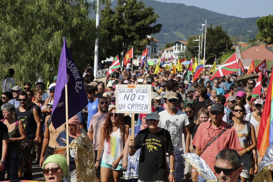 Demonstranten marschieren mit Flaggen und Plakaten während eines Protests gegen den G7-Gipfel.