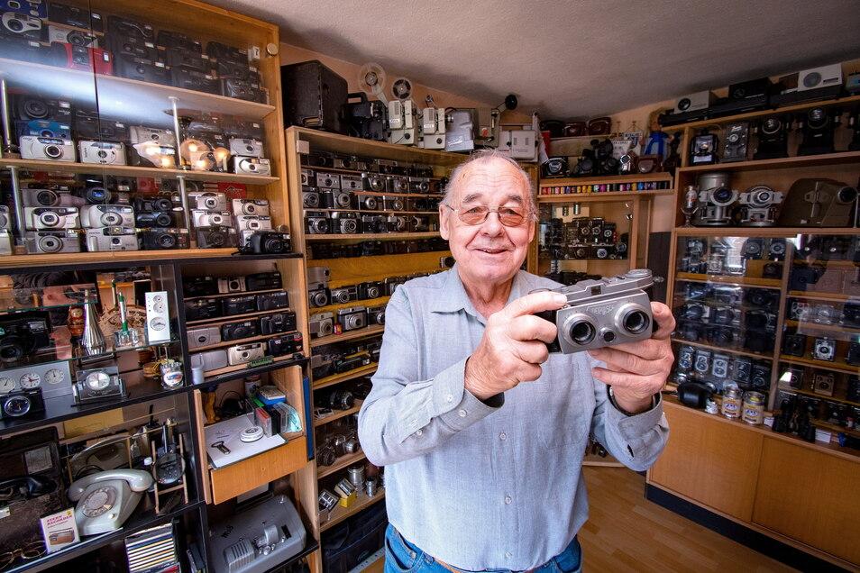 Alfred Kruggel steht in seiner Kamerasammlung. Er hat einen ganzen Raum mit Vitrinen und Hunderten Kameras gefüllt. In der Hand hält er eine Belplasca-Stereokamera, die in Dresden hergestellt wird.