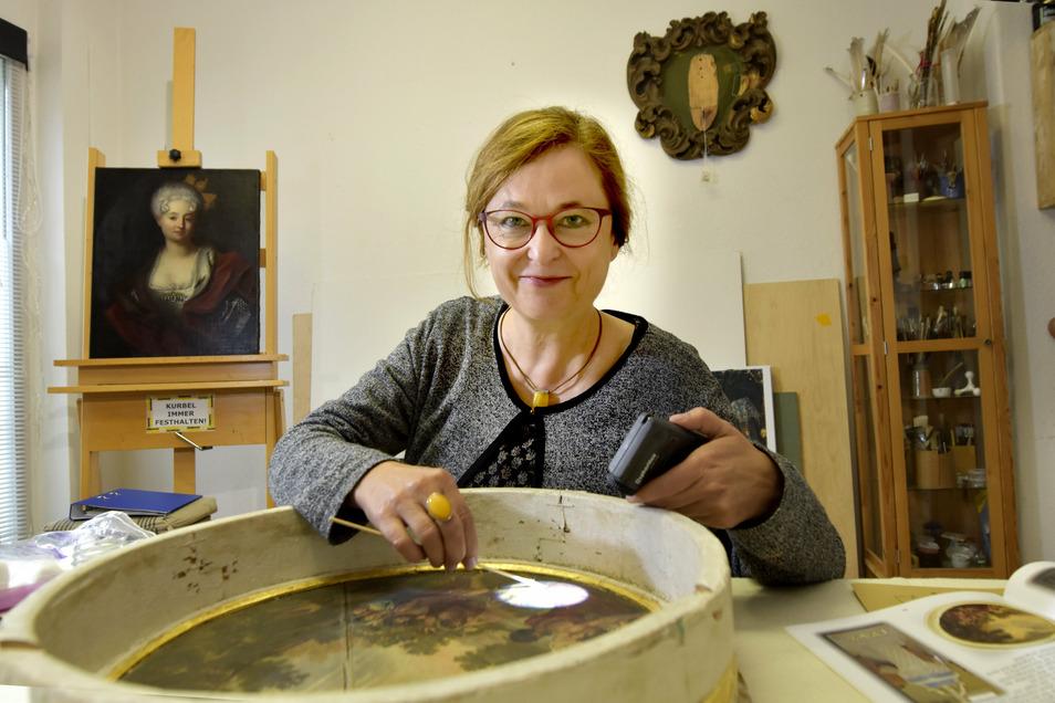 Die Restauratorin Anke Stenzel bei der Arbeit am Taufsteinbild in ihrem Atelier. Im Hintergrund ist das Gemälde aus der Rüstkammer mit Johanna Charlotte von Brandenburg-Schwedt zu sehen.