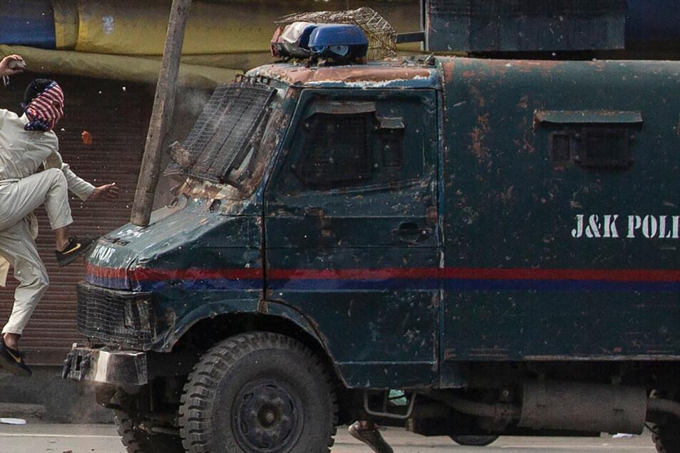 Ein maskierter kaschmirischer Demonstrant springt auf die Motorhaube eines gepanzerten Fahrzeugs der indischen Polizei, als er während einer Demonstration in Srinagar, dem von Indien kontrollierten Kaschmir,Steine darauf wirft. Das Bild ist Teil einer Fot