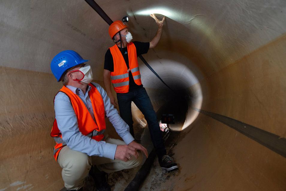 Chef-Stadtentwässerer Ralf Strothteicher und Bauleiter Martin Lehmann begutachteten den frisch sanierten Abwasser-Tunnel, bevor er wieder in Betrieb genommen wurde.