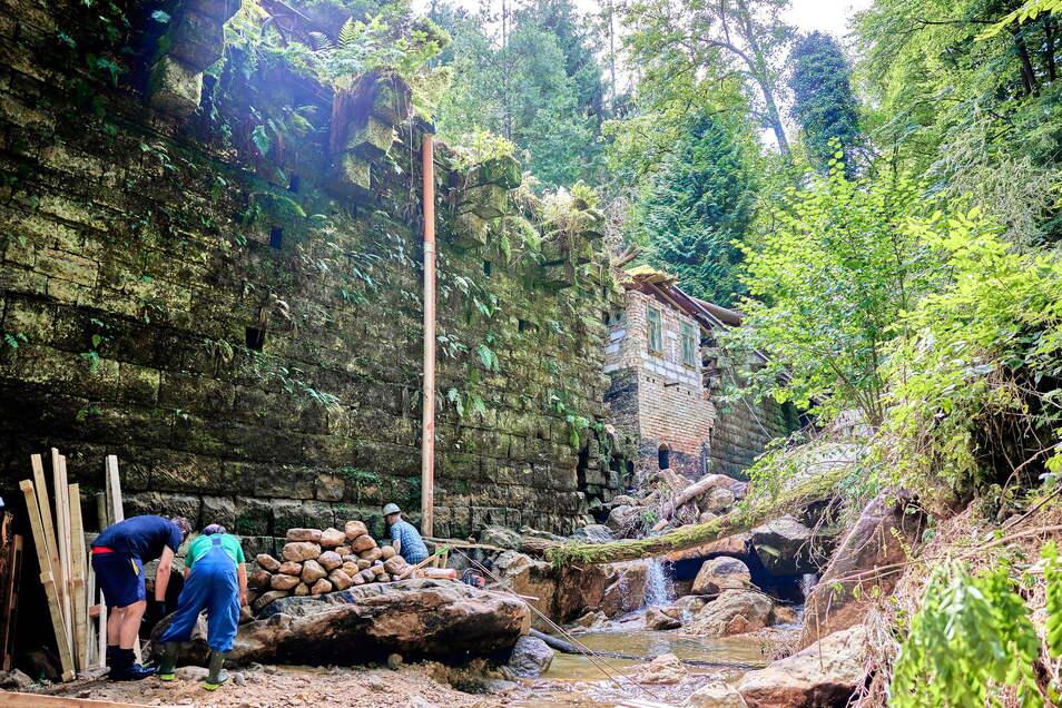 Kleine Männer, großes Bauwerk: Die Helfer holen Steine aus dem Bett des Mühlgrundbaches, um den Hohlraum in der Stützwand zu stabilisieren.
