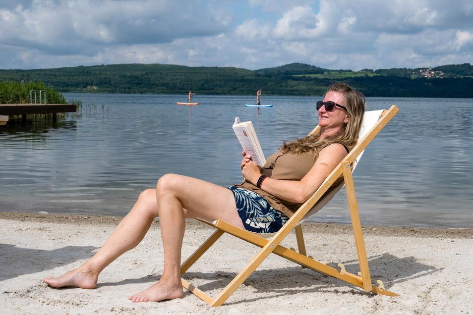 """Am Strand des Hotels """"Insel der Sinne"""" am Berzdorfer See findet diese Frau Ruhe und Entspannung. Stand-up-Paddler auf dem See genießen ebenfalls die Atmosphäre."""