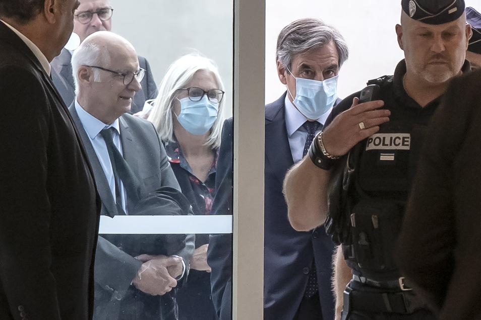 Francois Fillon (Mitte, r) und seine Frau Penelope (Mitte, l) tragen Mundschutz, als sie im Gerichtsgebäude eintreffen.