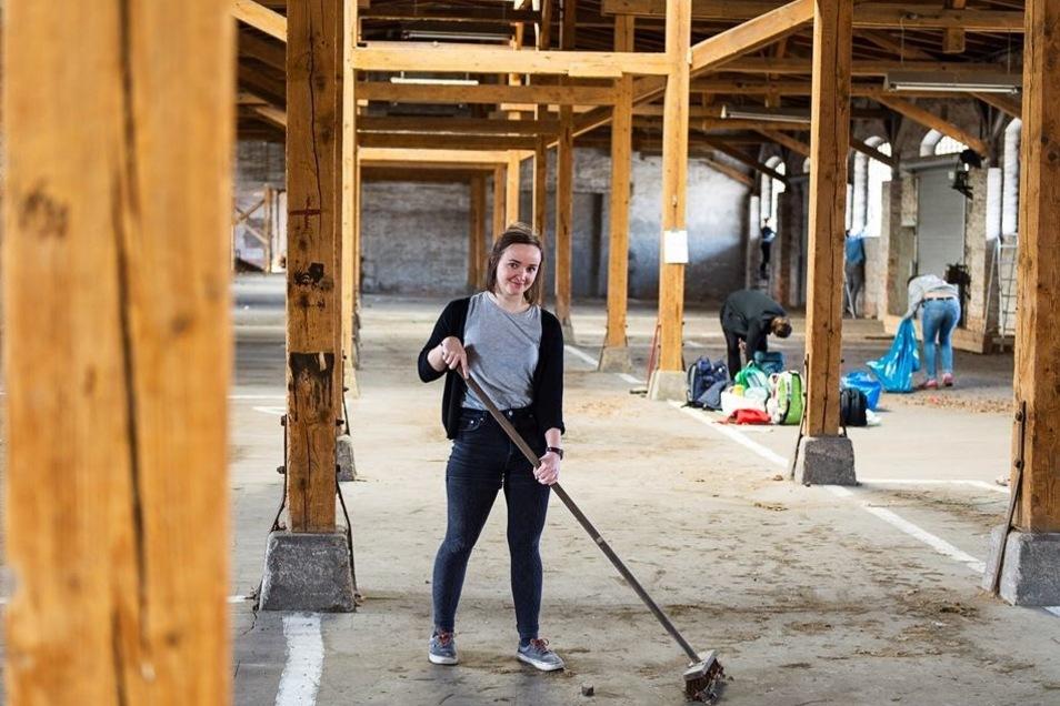 Kultur- und Management-Studentin Marielene Groß kehrt in einer der Hallen im Güterbahnhof den Dreck weg. Hier findet vom 5. bis 12. Mai das Zukunftsvisionen-Festival statt.