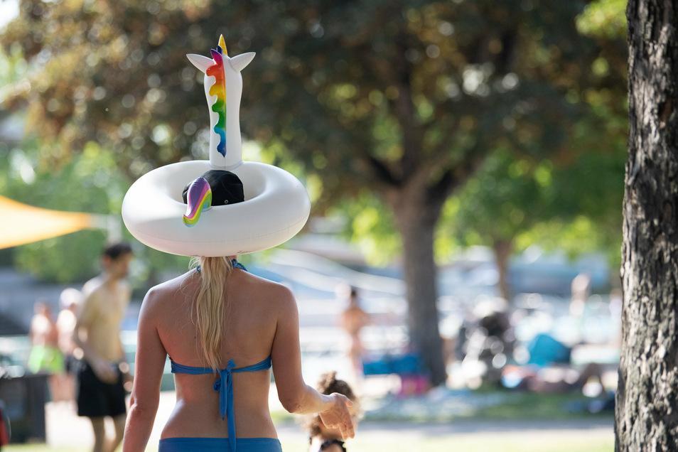 Eine Frau trägt einen Einhorn-Schwimmring auf dem Kopf.