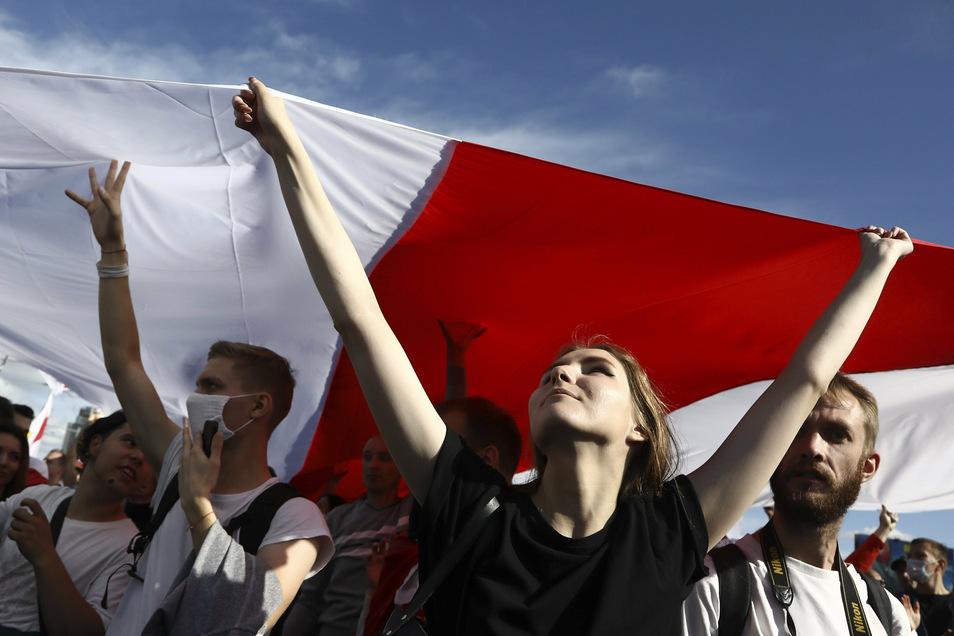 Belarus, Minsk: Demonstrantinnen und Demonstranten halten eine historische belarussische Flagge und nehmen an einem Protest der Opposition teil.