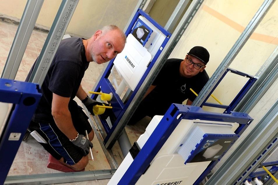 Jörg Schiemann und Steven Burghardt wechseln in den Toiletten Module und Leitungen aus.
