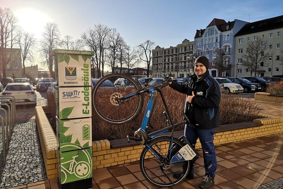 SWW-Mitarbeiter Robyn Brandt mit E-Bike vor einer Ladesäule.