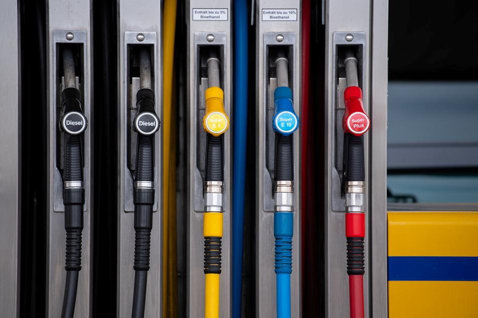 Zapfpistolen für verschiedene Kraftstoffarten hängen an einer Zapfsäule an einer Tankstelle.