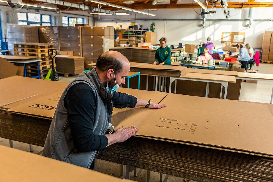 Für den Transport der Waren werden Kartons vorbereitet: Kleben, Falten, Bestücken. Nur einige wenige Mitarbeiter befinden sich in dieser Werkhalle, wo sonst etwa 50 Angestellte in der Industriemontage tätig sind.