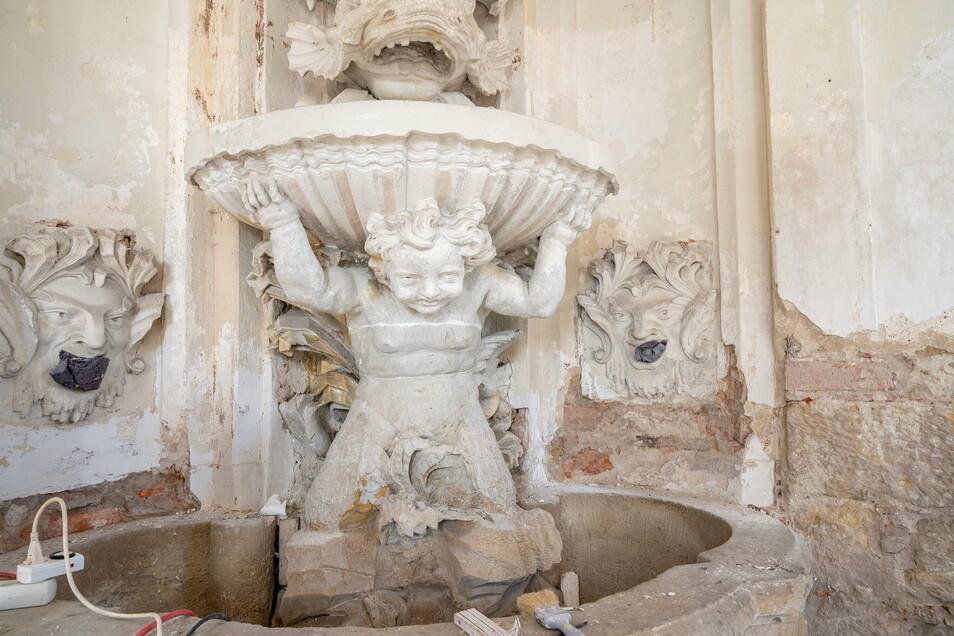 Ein Triton hält die untere Schale eines von zwei Wasserspielen, die noch im Inneren des Grottenpavillons erhalten sind.