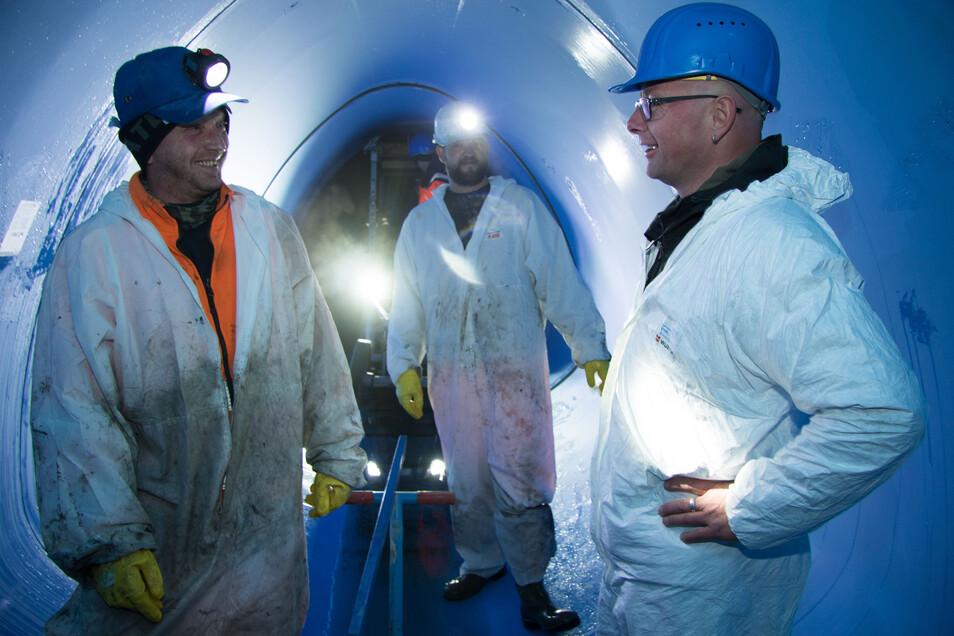 Projektleiter Heiko Nytsch (r.) freut sich, dass die Kanalsanierung so zügig voran geht. Die Kanalsanierer Thomas Haase (l.) und Martin Krug haben gerade das nächste Kunststoffrohr an die Röhre angefügt.