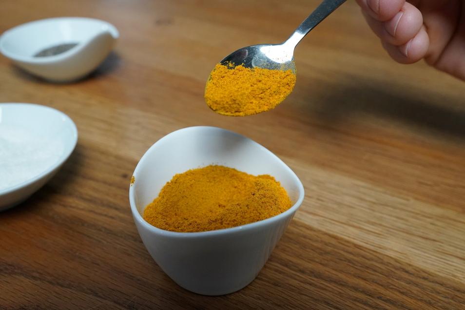 Ein Mann hält einen Löffel mit Currywurst-Gewürz in der Hand. Immer mehr Gerichte und ihre Namen werden infrage gestellt.
