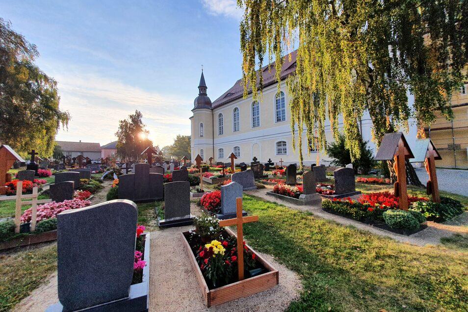 Die Kirche ist in Crostwitz von zentraler Bedeutung, gerade wird sie aufwendig saniert. Auch auf dem Friedhof sprießen aus allen Gräbern frische Blumen, kein einziges ist ungepflegt.