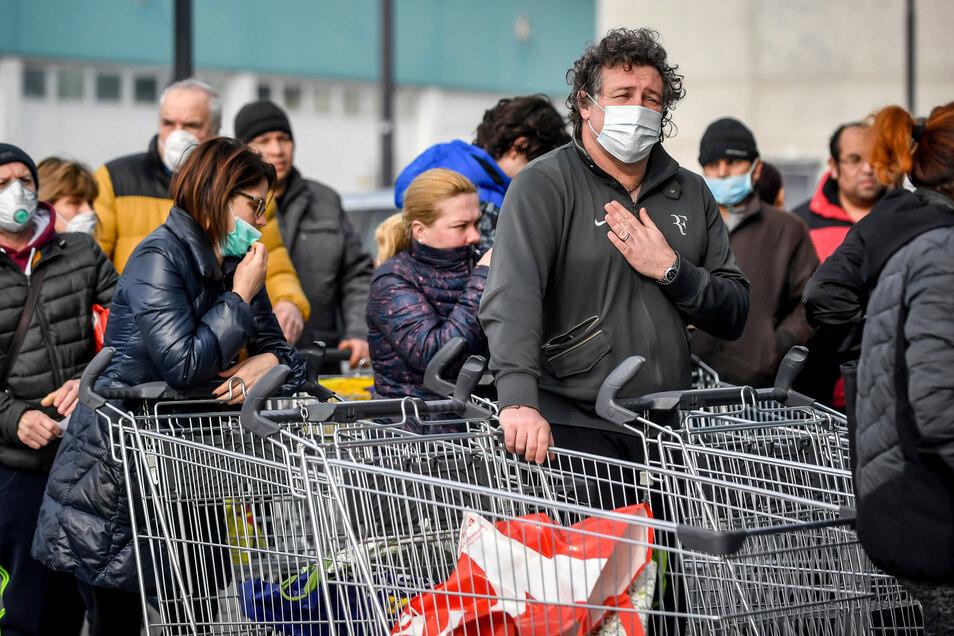 Italien, Casalpusterlengo: Menschen tragen Atemschutzmasken und stehen vor einem Supermarkt in einer Schlange. Nach dem Tod zweier Menschen sind Teile des öffentlichen Lebens zum Erliegen gekommen.