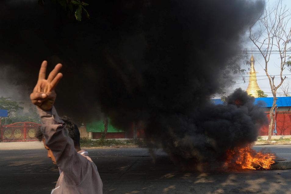 Ein Demonstrant zeigt in Yangon den Dreifingergruß als Zeichen des Widerstands.