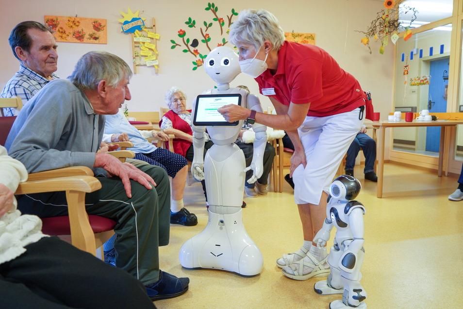 Ergotherapeutin Carola Gnauck erklärt Heimbewohnern die Bedienung von Roboter Thea.