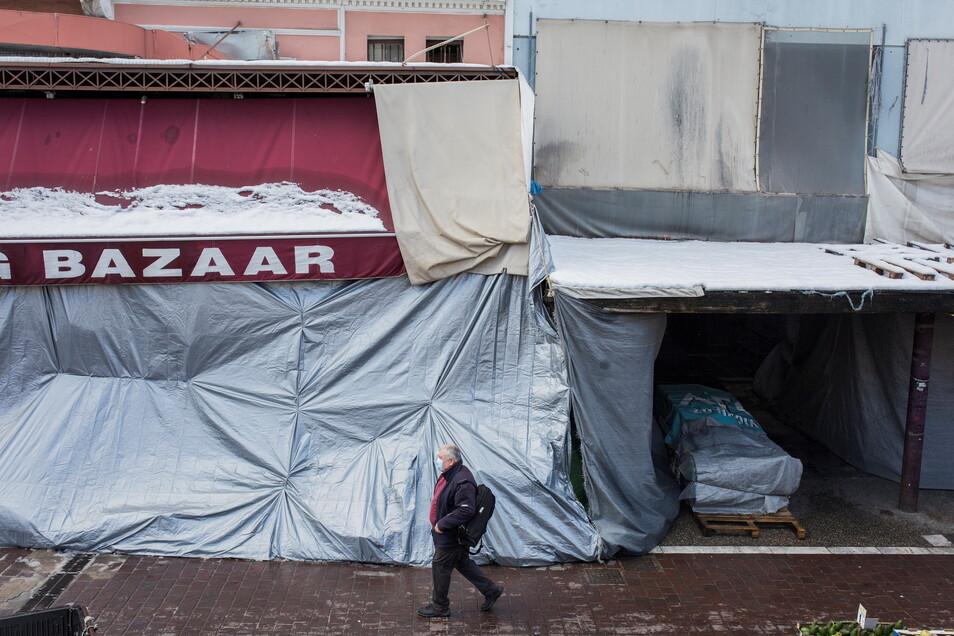 Ein Mann geht auf dem Hauptmarkt von Athen an geschlossenen Geschäften vorbei.