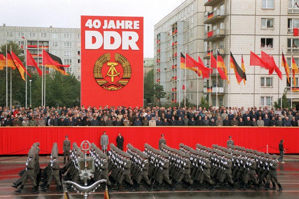 Das Archivbild zeigt Soldaten der Nationalen Volksarmee während der Militärparade in Ost-Berlin vor der Tribüne mit der Regierung und den Ehrengästen auf der Karl-Marx-Allee. Die Führung der DDR feierte die Gründung der Deutschen Demokratischen Republik v
