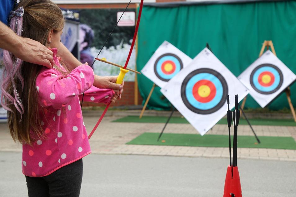 Flora aus Riesa übt beim Tag der Sachsen am Stand des Landessportbundes das Bogenschießen.