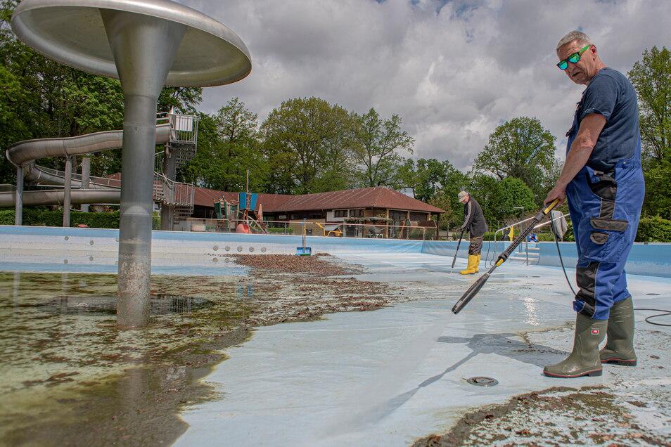 Andreas Kaiser (vorn) und Rochus Mahler reinigen das Becken im Königsbrücker Erlebnisbad., damit neues Wasser eingelassen werden kann.