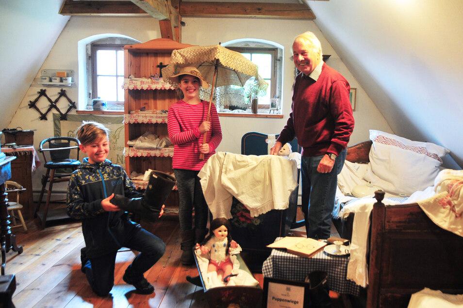 Leiter Reinhard Krönert, hier mit Schülern auf dem Dachboden des Heimatmuseums Weinböhla, hofft, dass die Sonderausstellung der Leisten wie auch schon im Wasserschloss Oberau, zahlreiche Besucher anziehen wird.
