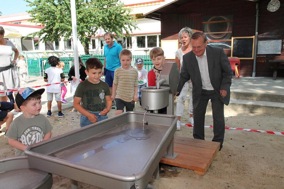 Das erste Wasser pumpen die Kinder und Stiftungsratsmitglied Thomas Delling gemeinsam in die Anlage.