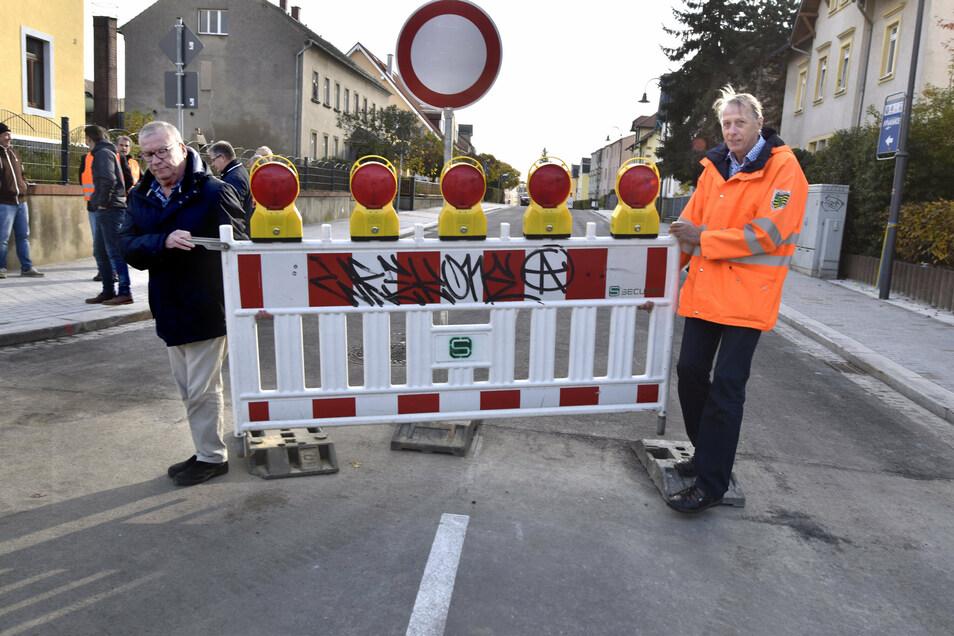Radebergs OB Gerhard Lemm (SPD) und Jürgen Israel, Abteilungsleiter im Landestraßenamt räumten auf der Dr.-Rudolf-Friedrichs-Straße die Sperrzäune beiseite.