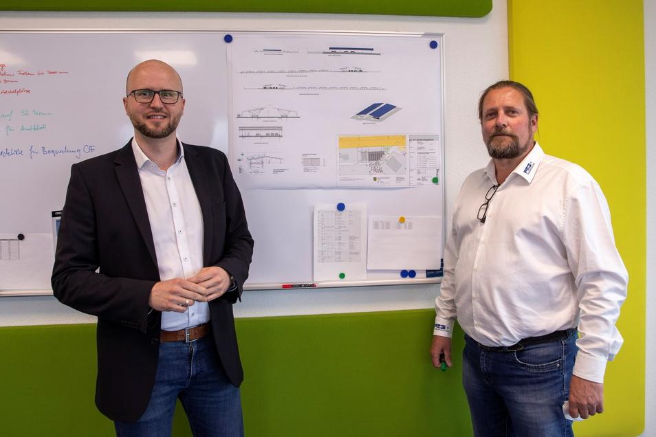 David Riedrich (links) und Torsten Freudenberg, Geschäftsführer der Firma PGM Precision Mechanics Group GmbH, zeigen in ihrem Büro den Bauplan der Solaranlage.