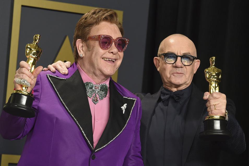 Elton John (l) und Bernie Taupin zeigen ihren Oscar für das beste Originallied.