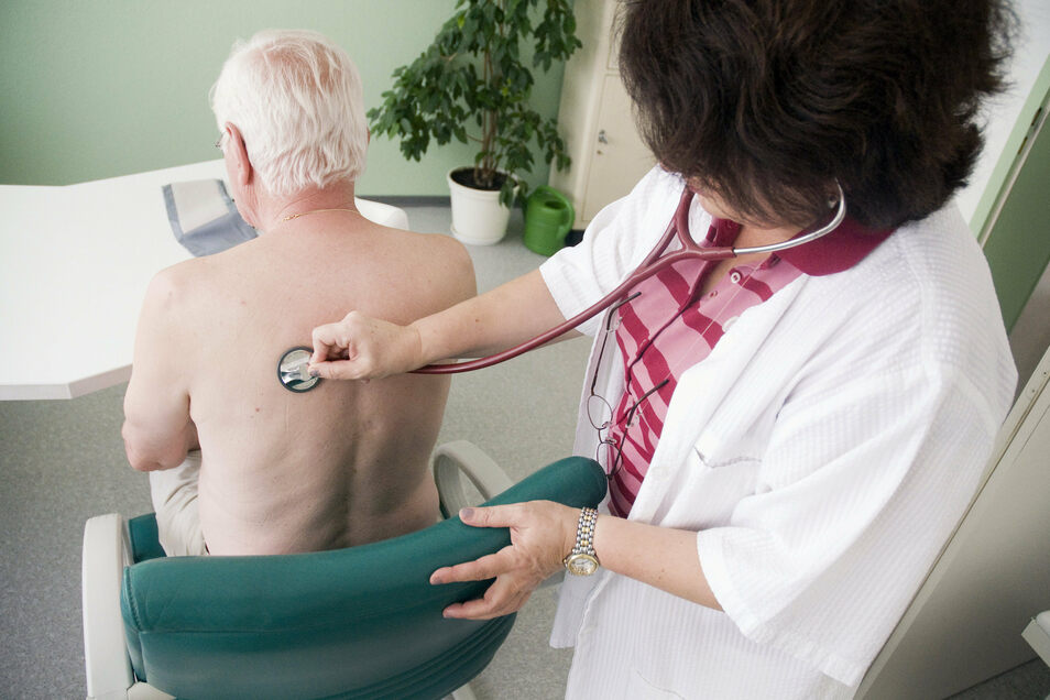 Eine Hausärztin untersucht am in ihrer Praxis einen Patienten.