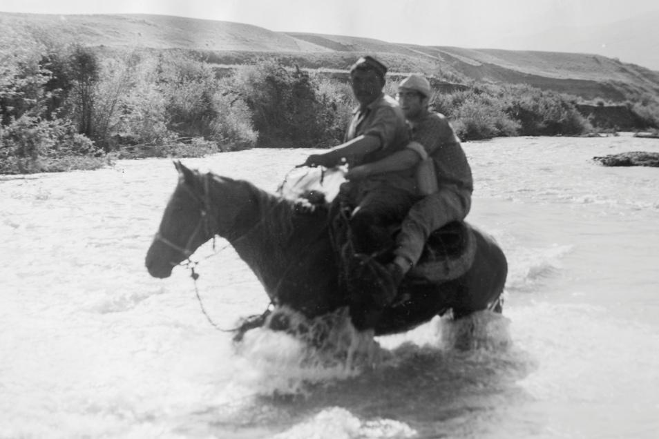 Wieder mal keine Brücke da: Ein einheimischer Hirte setzt die Wanderer mittels Pferd über den Koksu-Fluss in Tadschikistan.