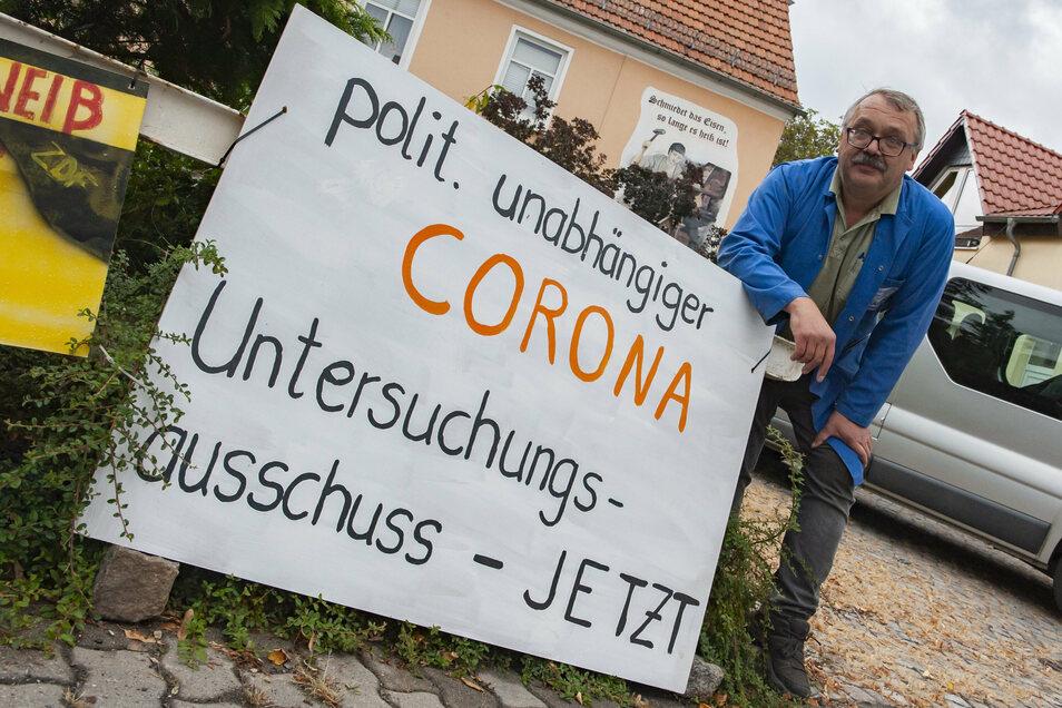 Gerald Bauer in Schönfeld an einem Corona-Protestplakat. Sieben hängen insgesamt im Ort.