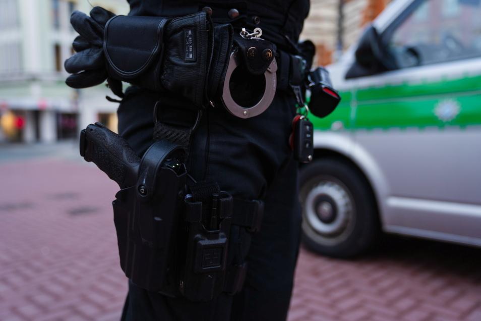 Ein Polizeibeamter steht in der Fußgängerzone von Hof neben seinem Einsatzfahrzeug.
